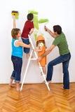 Família feliz que redecorating a casa - pintura Fotografia de Stock