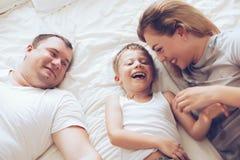 Família feliz que relaxa na cama Imagem de Stock