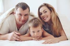 Família feliz que relaxa na cama Imagens de Stock