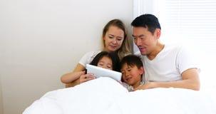 Família feliz que relaxa na cama e que usa a tabuleta digital vídeos de arquivo