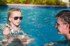 Família feliz que relaxa na piscina fotos de stock