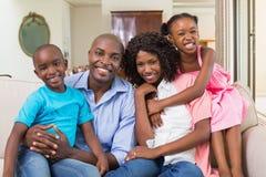 Família feliz que relaxa no sofá fotografia de stock
