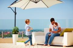 Família feliz que relaxa no sofá no terraço da parte superior do telhado no dia ensolarado morno Fotografia de Stock