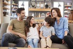 Família feliz que senta-se em Sofa In Lounge Talking Together foto de stock royalty free