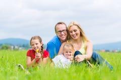 Família feliz que senta-se fora na grama Imagens de Stock Royalty Free