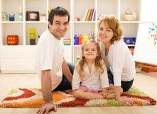 Família feliz que senta-se junto no assoalho Imagens de Stock