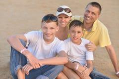 Família feliz que senta-se na areia imagem de stock