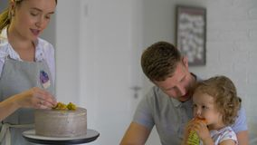 Família feliz que senta-se na cozinha, mum que decora o bolo do fruto video estoque