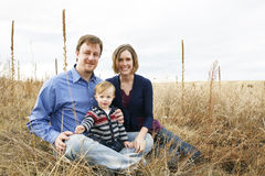 Família feliz que senta-se no campo imagem de stock