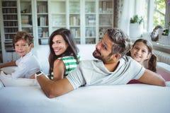 Família feliz que senta-se no sofá foto de stock