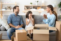Família feliz que senta-se no sofá na casa nova imagens de stock