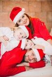Família feliz que senta-se perto da árvore de Natal No vermelho Fotografia de Stock Royalty Free