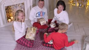 Família feliz que senta-se perto da chaminé e dos presentes de Natal gifting no ev do feriado video estoque
