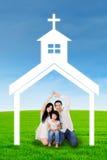 Família feliz que senta-se sob o símbolo da igreja Fotos de Stock Royalty Free