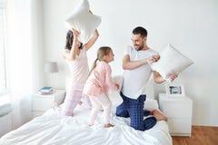 Família feliz que tem a luta de descanso na cama em casa Imagem de Stock