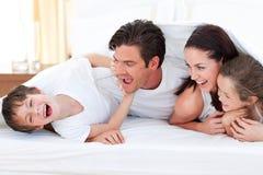 Família feliz que tem o divertimento encontrar-se na cama fotografia de stock