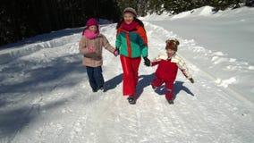 Família feliz que tem o divertimento que joga em uma floresta nevado nas montanhas no inverno Mamã e suas duas crianças Correm fe filme