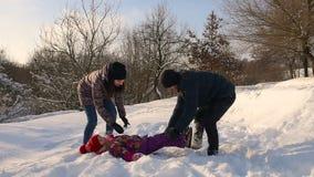 Família feliz que tem o divertimento que joga na neve filme
