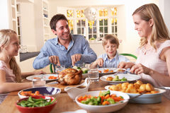 Família feliz que tem o jantar da galinha de assado na tabela