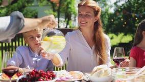 Família feliz que tem o jantar ou o partido de jardim do verão filme