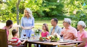 Família feliz que tem o jantar ou o partido de jardim do verão foto de stock