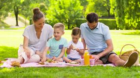 Família feliz que tem o piquenique no parque do verão filme