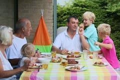 Família feliz que tem a refeição junto fotografia de stock
