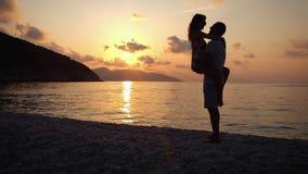 Família feliz que tem um divertimento na praia no por do sol sobre o mar Metragem lenta do molion video estoque