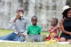Família feliz que toma parte num piquenique no parque fotos de stock royalty free