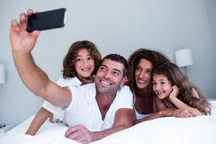 Família feliz que toma um selfie na cama fotografia de stock