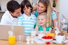 Família feliz que usa o portátil durante o pequeno almoço imagem de stock
