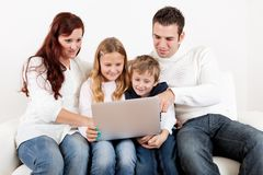 Família feliz que usa o portátil em casa Imagens de Stock