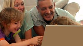 Família feliz que usa o portátil junto