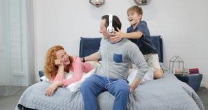 Família feliz que usa os fones de ouvido novos que escutam a música no quarto que passa o tempo junto na manhã