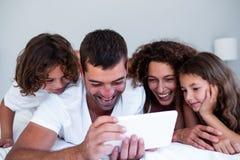 Família feliz que usa a tabuleta digital na cama imagem de stock royalty free