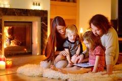 Família feliz que usa um PC da tabuleta por uma chaminé fotos de stock