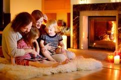Família feliz que usa um PC da tabuleta por uma chaminé Imagens de Stock