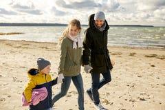Família feliz que vai tomar parte num piquenique na praia no outono imagem de stock royalty free