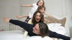 A família feliz que veste pijamas está tendo o divertimento no quarto Duas crianças de Playfull com cabelo encaracolado e pares n filme