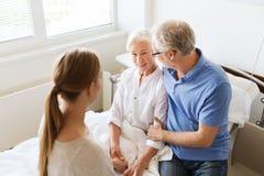 Família feliz que visita a mulher superior no hospital Imagem de Stock