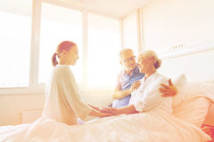 Família feliz que visita a mulher superior no hospital foto de stock royalty free