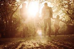Família feliz satisfeita que salta altamente no parque fotografia de stock