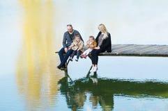 A família feliz senta-se no cais no dia morno do outono que oscila seus pés na água fotografia de stock