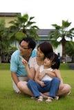 A família feliz senta-se no campo de grama Imagens de Stock
