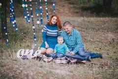 A família feliz tem a festa de anos com as decorações azuis na floresta Foto de Stock Royalty Free