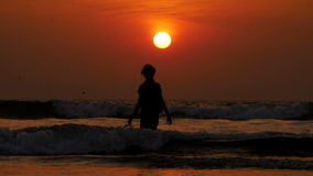 A família feliz tem o divertimento e o por do sol de observação na praia vídeos de arquivo