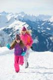 A família feliz tem o divertimento nas montanhas em um dia de inverno ensolarado Fotos de Stock Royalty Free