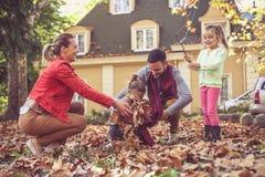 A família feliz tem o jogo na parte dianteira do quintal No movimento imagem de stock