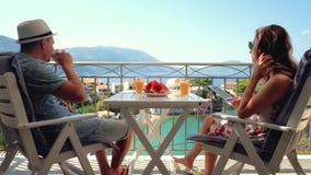 A família feliz tem um café da manhã que senta-se no balcão no fundo bonito da ilha filme