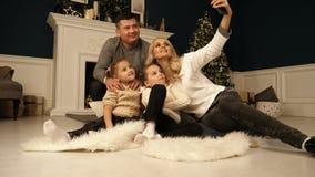 Família, feriados, tecnologia e povos - mãe de sorriso, pai e meninas que fazem o selfie com câmera sobre vídeos de arquivo